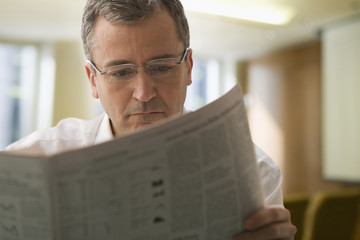 Caucasian businessman reading newspaper
