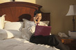 Chinese businessman using laptop in hotel room