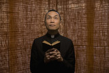 Pacific Islander priest praying