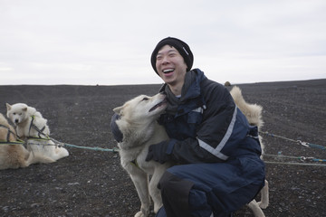 Chinese man petting dog in dog sled pack