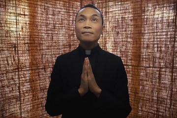 Pacific Islander priest praying