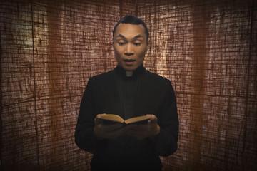 Pacific Islander priest reading bible