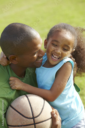 African American father hugging daughter