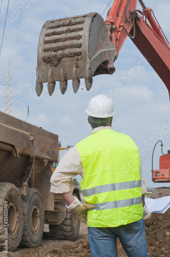 Hispanic construction worker watching backhoe
