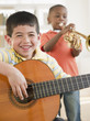 Boys playing trumpet and guitar