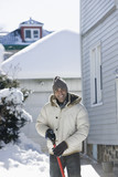 Mixed race man shoveling snow off driveway