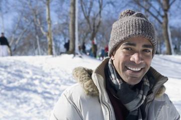 Mixed race man in cap and coat outdoors