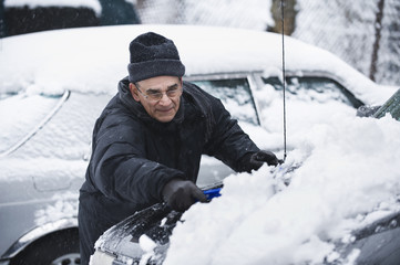 Hispanic man removing snow from car