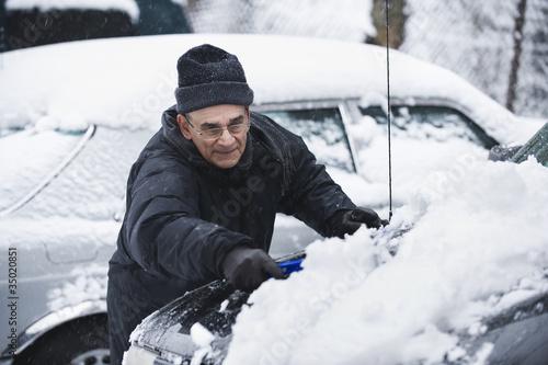 Hispanic man removing snow from car