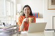 Chinese businesswoman drinking coffee at desk