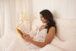Middle Eastern woman reading in bed