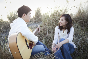 Korean man playing guitar for girlfriend