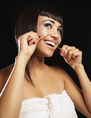 Mixed race woman flossing her teeth