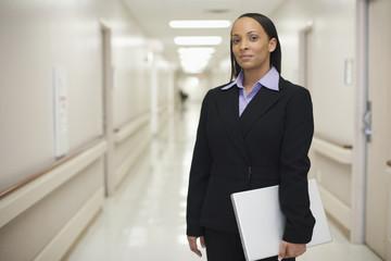 Black businesswoman standing in hospital hallway