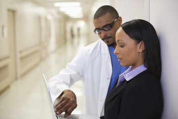 Doctor and administrator looking at laptop in hallway