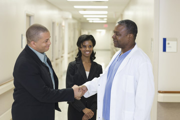Doctor greeting administrators in hospital hallway