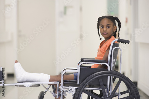 African American girl with broken leg sitting in wheelchair