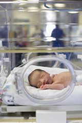 Hispanic baby asleep in intensive care unit