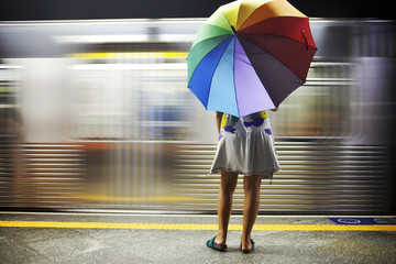Mixed race woman with umbrella on train platform