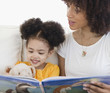 Woman reading book with daughter
