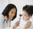Pediatrician with otoscope examining patient