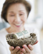 Japanese woman holding nest filled with money