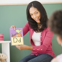 Black teacher showing letter d flash card to student