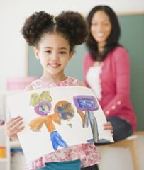 Proud student holding painting in classroom