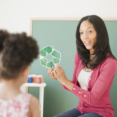 Teacher showing recycling symbol to student