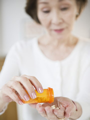 Japanese woman pouring medicine into hand