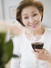 Japanese holding glass of red wine