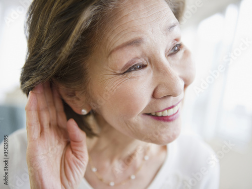 Japanese woman listening with hand near ear