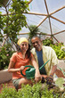 Woman and man with watering can in greenhouse
