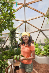 Ecuadorian woman holding potted plant in greenhouse