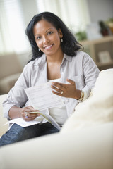 Hispanic woman sitting on sofa holding bills