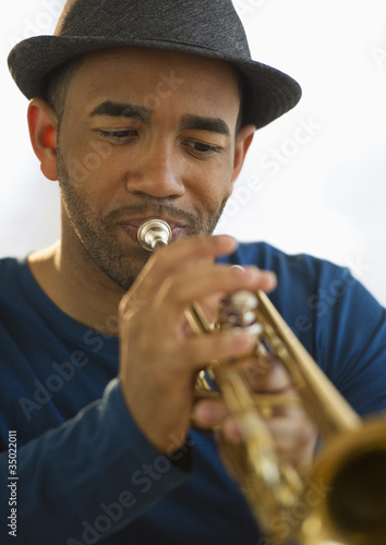Mixed race man playing trumpet
