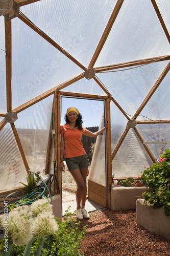 Ecuadorian woman posing in doorway of greenhouse