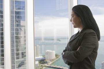 Hispanic businesswoman with arms crossed near window