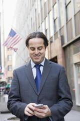Hispanic businessman text messaging in city