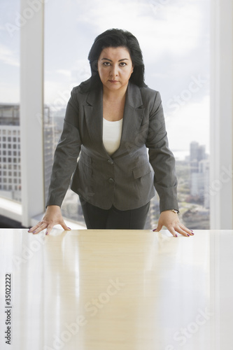 Hispanic businesswoman leaning on desk