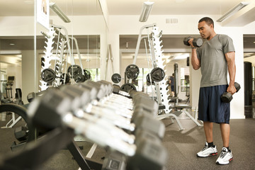 African American man lifting hand weights in health club