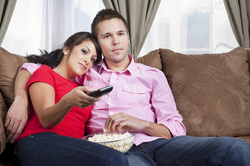 Couple sitting on sofa and watching television