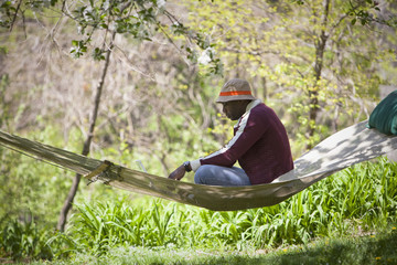 Black man sitting in hammock
