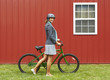 Mixed race woman in helmet standing with bicycle