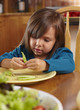 Mixed race girl shelling pea pod at dining table