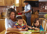 """""""Mother, son and daughter shelling peas at dining table"""""""