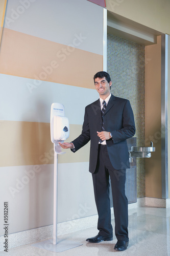 Hispanic businessman using hand sanitizer in lobby