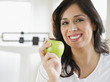 Smiling Hispanic woman holding a green apple
