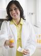 Smiling Hispanic pharmacist holding out prescription bottle