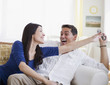 Laughing mixed race man keeping remote control away from wife